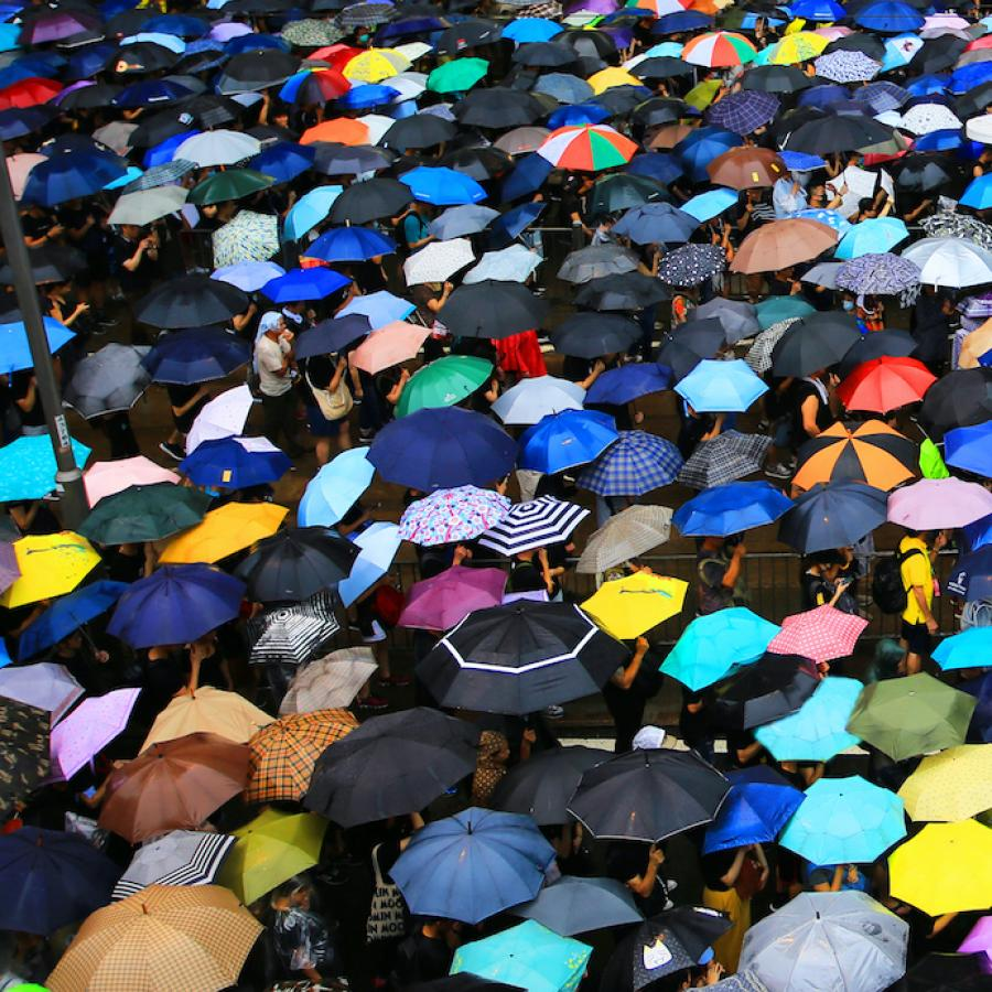 crowds of people protected by umbrellas